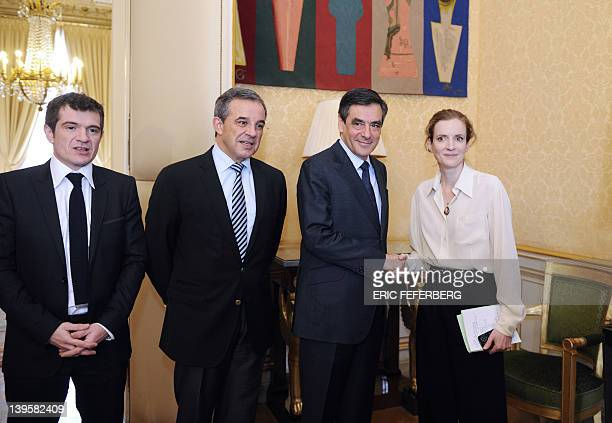 France's Ecology and Sustainable Minister Nathalie KosciuskoMorizet shakes hands with France's Prime Minister Francois Fillon flanked by Housing...