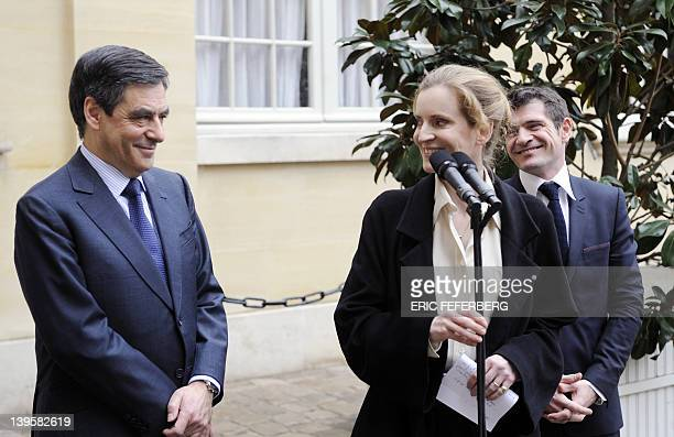 France's Ecology and Sustainable Minister Nathalie KosciuskoMorizet smiles at France's Prime Minister Francois Fillon as she delivers a speech...
