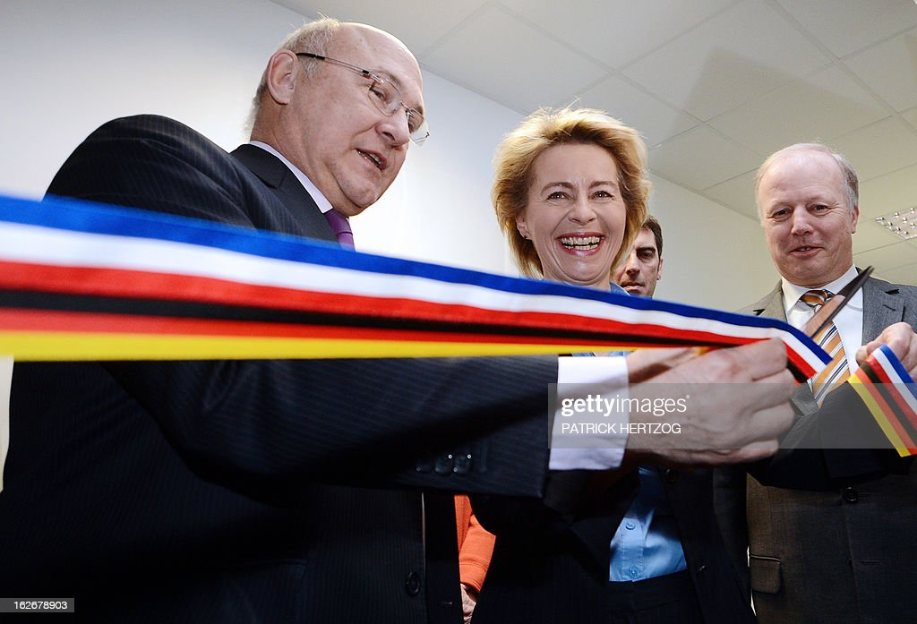 France's Employment Minister Michel Sapin (L) and his German counterpart Labour and Social Affairs Minister Ursula von der Leyen (C) cut the ribbon on February 26, 2013 in Kehl, south-western Germany, during the inauguration ceremony for the opening of the first binational job center. Pole emploi and Agentur fur Arbeit signed a cooperation agreement for the placement of cross-border jobless.