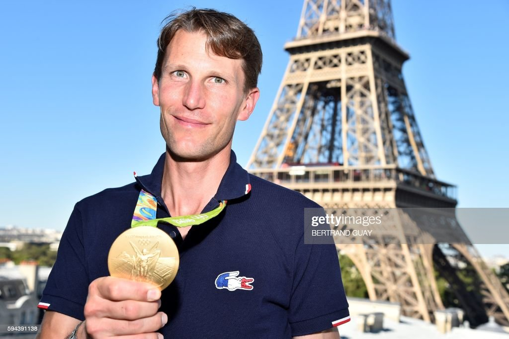 France's Equestrian Jumping team rider Kevin Staut poses with his gold medal on August 23 in front of the Eiffel tower in Paris France's Olympic team...