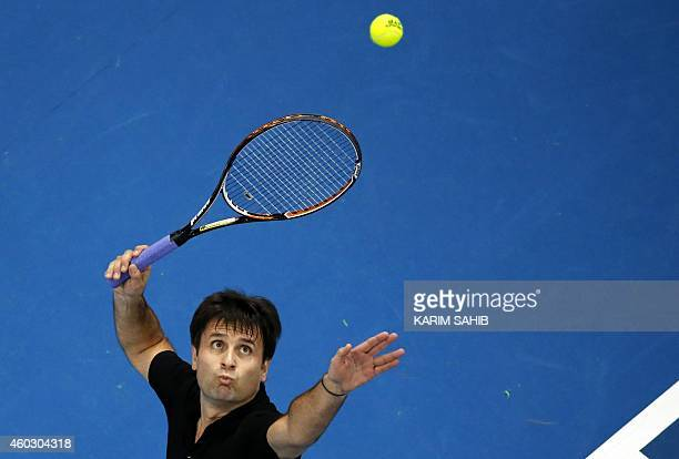 France's Fabrice Santoro of the Indian Aces serves to Australian Patrick Rafter of the Singapore Slammers during the CocaCola International Premier...
