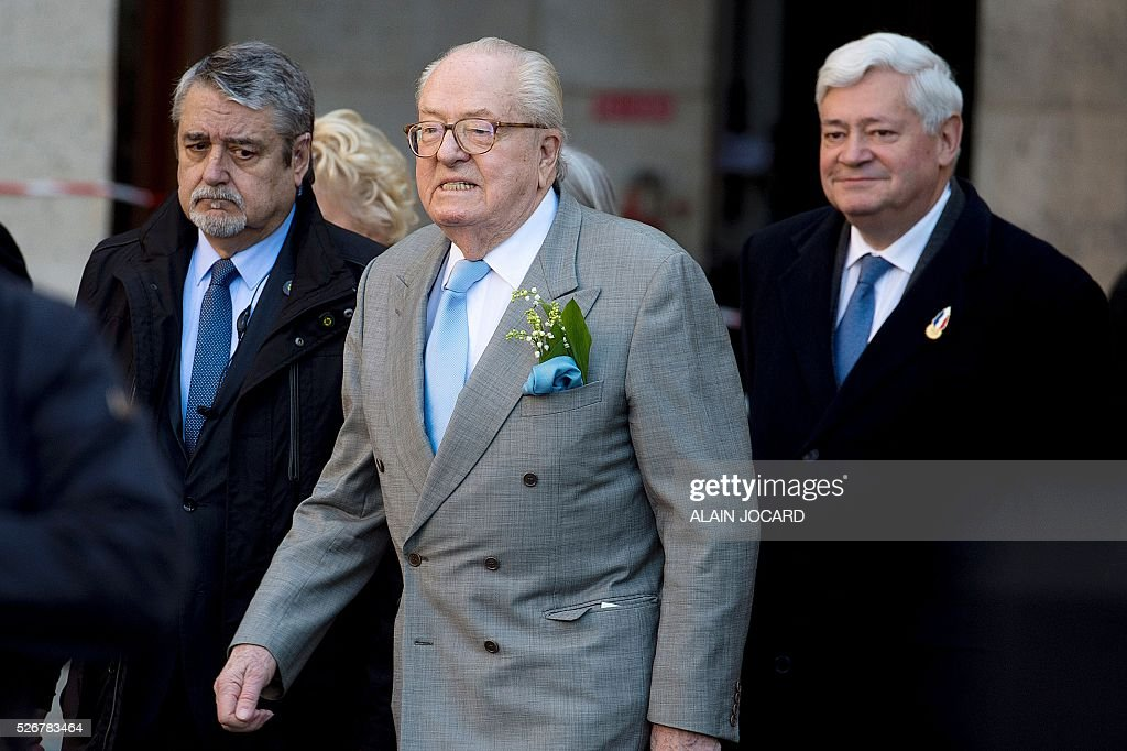 France's far-right Front National (FN) party founder and former leader Jean-Marie Le Pen (C) arrives with FN European parliament member Bruno Gollnisch to deliver a speech at the Place des Pyramides in Paris during a rally in honour of Jeanne d'Arc (Joan of Arc) on May 1, 2016. / AFP / ALAIN