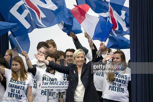 France's farright Front National party president Marine Le Pen waves to supporters after delivering a speech on stage at the Place de l'Opera during...