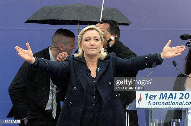 France's farright National Front leader Marine Le Pen gestures at supporters during a May Day rally in Paris on May 1 2014 AFP PHOTO / PIERRE ANDRIEU