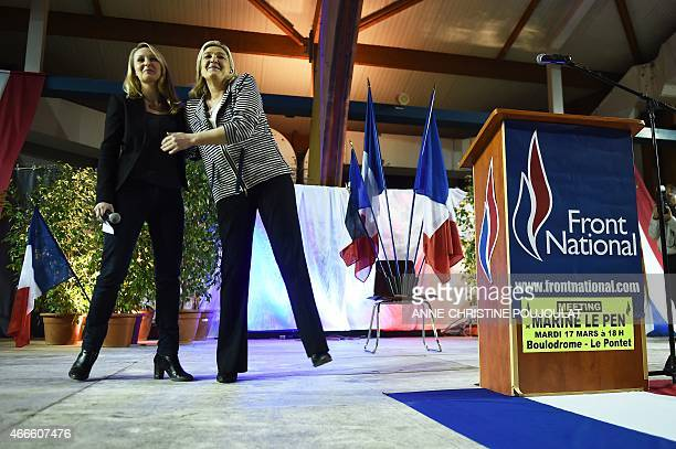 France's farright National Front party leader Marine Le Pen embraces FN member of the parliament Marion Marechal Le Pen during a meeting on March 17...