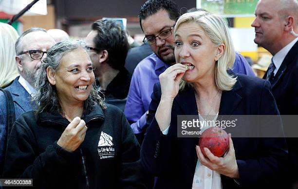 France's farright National Front party president Marine Le Pen eats a mango as she visits the Paris international agricultural fair at the Porte de...