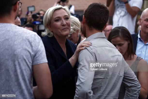 France's farright National Front Party President Marine Le Pen greets supporters after delivering a speech after the polls closed during the second...