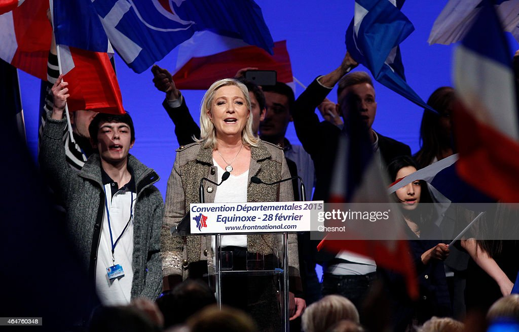 France's farright National Front party President Marine Le Pen stands on stage with supporters waving French National flags at the end of her speech...