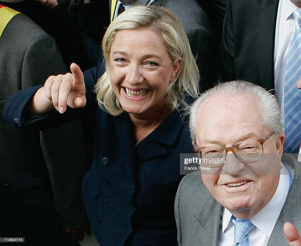 France's far-right National Front President, <a gi-track='captionPersonalityLinkClicked' href=/galleries/search?phrase=Marine+Le+Pen&family=editorial&specificpeople=588282 ng-click='$event.stopPropagation()'>Marine Le Pen</a> (L) and her father <a gi-track='captionPersonalityLinkClicked' href=/galleries/search?phrase=Jean-Marie+Le+Pen&family=editorial&specificpeople=214017 ng-click='$event.stopPropagation()'>Jean-Marie Le Pen</a> take part in a march as part of the party's annual celebration of Joan of Arc on May 1, 2011 in Paris, France. France's far-right National Front members took part in its traditional Joan of arc May Day Rally with the party's new leader, as thousands across the globe took to the streets to rally for worker's rights on International Workers' Day.