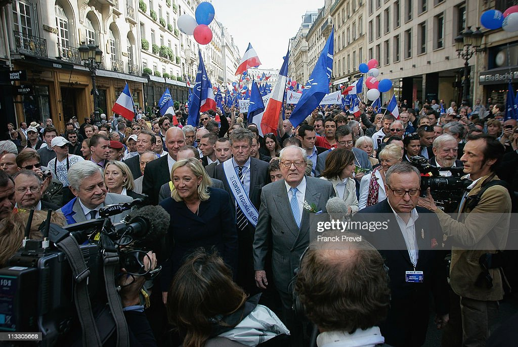 France's far-right National Front President, Marine Le Pen (C) and her father Jean-Marie Le Pen takes part in a march as part of the party's annual celebration of Joan of Arc on May 1, 2011 in Paris, France. France's far-right National Front members took part in its traditional Joan of arc May Day Rally with the party's new leader, as thousands across the globe took to the streets to rally for worker's rights on International Workers' Day.