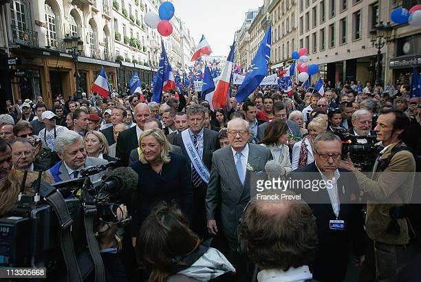 France's farright National Front President Marine Le Pen and her father JeanMarie Le Pen takes part in a march as part of the party's annual...