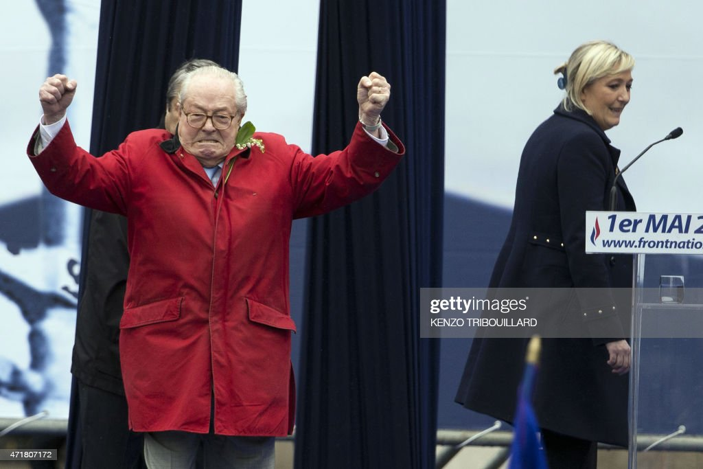 France's far-right political party Front National (FN) founder and honorary president, <a gi-track='captionPersonalityLinkClicked' href=/galleries/search?phrase=Jean-Marie+Le+Pen&family=editorial&specificpeople=214017 ng-click='$event.stopPropagation()'>Jean-Marie Le Pen</a> gestures on stage as FN's president <a gi-track='captionPersonalityLinkClicked' href=/galleries/search?phrase=Marine+Le+Pen&family=editorial&specificpeople=588282 ng-click='$event.stopPropagation()'>Marine Le Pen</a> looks on during the party's annual rally in honour of Jeanne d'Arc (Joan of Arc) on May 1, 2015 in Paris. AFP PHOTO / KENZO TRIBOUILLARD