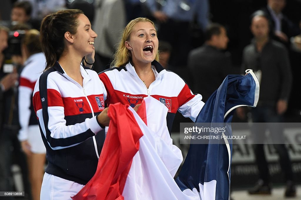 France's Fed Cup players Oceane Dodin (L) and Kristina Mladenovic celebrate after winning the Fed Cup World Group first round tennis match against Italy in Marseille, southern France, on February 7, 2016. / AFP / ANNE-CHRISTINE POUJOULAT