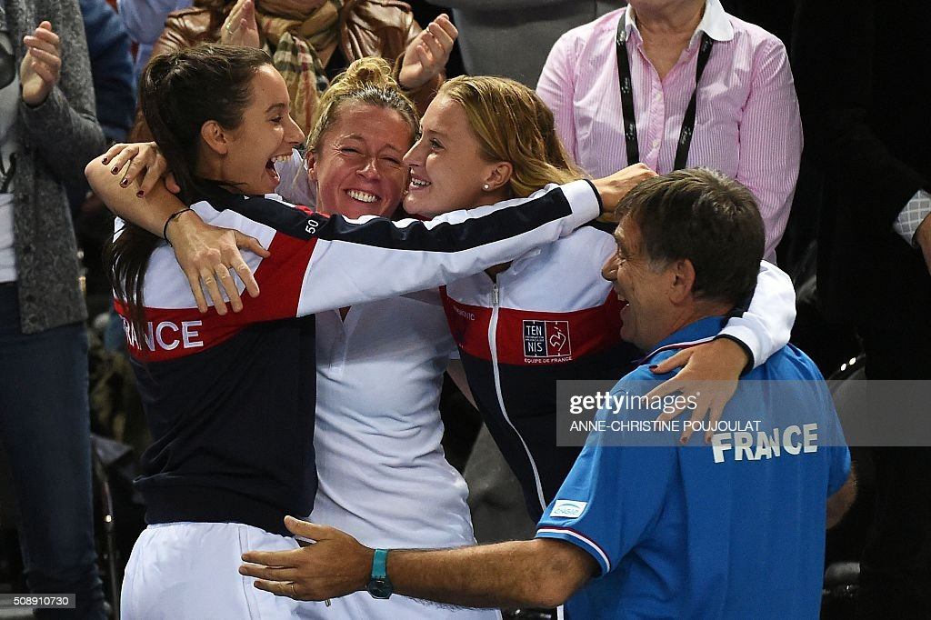 France's Fed Cup players Oceane Dodin, Pauline Parmentier and Kristina Mladenovic celebrate after winning the Fed Cup World Group first round tennis match against Italy in Marseille, southern France, on February 7, 2016. / AFP / ANNE-CHRISTINE POUJOULAT