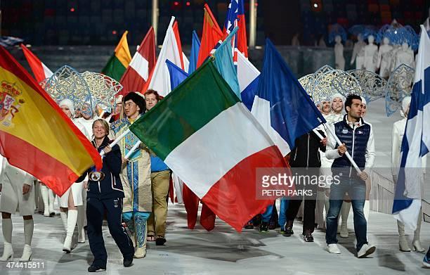 France's flag bearer biathlete Martin Fourcade and Italy's flag bearer short track skater Arianna Fontana enter the stadium during the Closing...