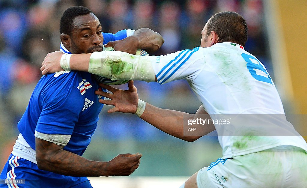France's flanker Fulgence Ouedraogo is tackled by Italy's N°8 and captain Sergio Parisse (R) during the Six Nations International Rugby Union match between Italy and France at the Olympic Stadium in Rome on February 3, 2013. AFP PHOTO / GABRIEL BOUYS