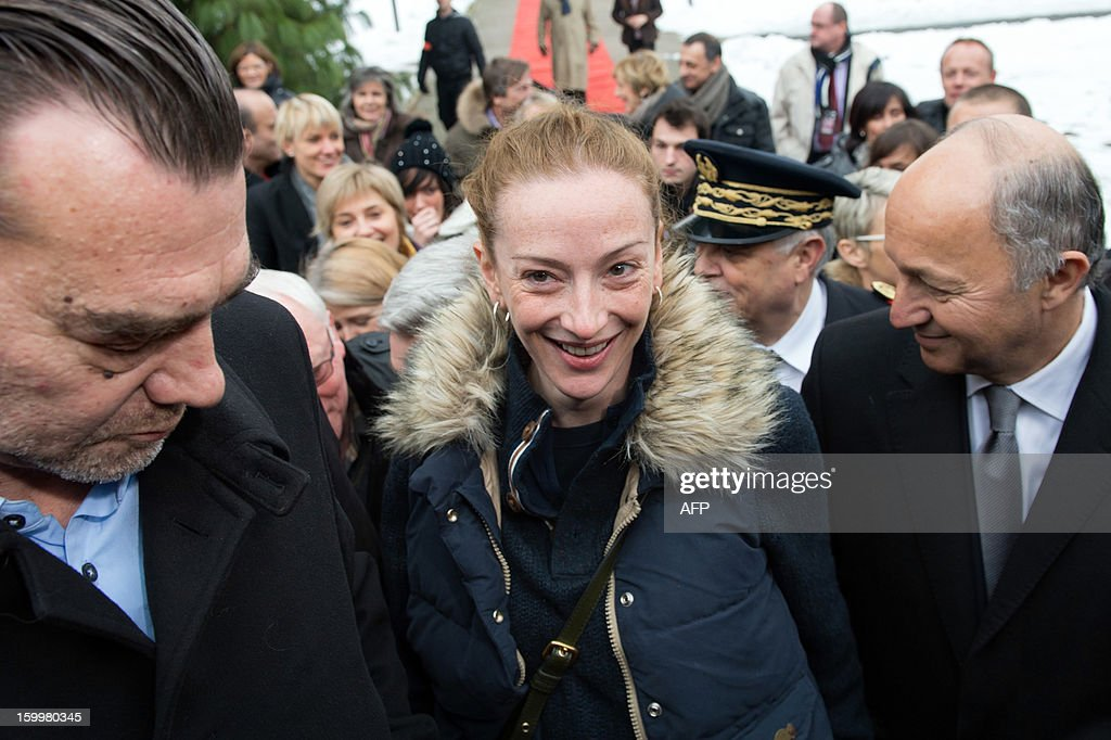 France's Florence Cassez, flanked by French Foreign minister Laurent Fabius (R) and her Lawyer Frank Berton, arrives for a press conference at Roissy airport on January 24, 2013 in Roissy-en-France where she landed after being freed from a Mexican prison the day before following a Supreme Court ruling that police violated her rights by staging her arrest for kidnapping on national television seven years ago. After facing 60 years in jail, Cassez, 38, took a flight to Paris, hours after three of five justices voted for her immediate release in a case that had strained Franco-Mexican ties. AFP PHOTO / BERTRAND LANGLOIS