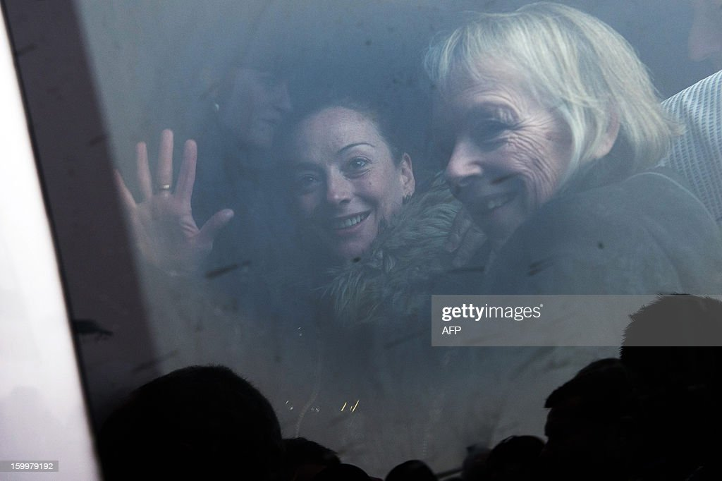 France's Florence Cassez (L) gestures, next to her mother Charlotte, from a minivan at Roissy airport on January 24, 2013 in Roissy-en-France where she landed after being freed from a Mexican prison the day before following a Supreme Court ruling that police violated her rights by staging her arrest for kidnapping on national television seven years ago. After facing 60 years in jail, Cassez, 38, took a flight to Paris, hours after three of five justices voted for her immediate release in a case that had strained Franco-Mexican ties. AFP PHOTO / BERTRAND LANGLOIS