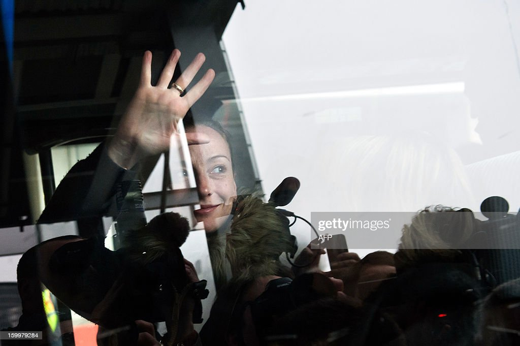 France's Florence Cassez gestures waves from a minivan at Roissy airport on January 24, 2013 in Roissy-en-France where she landed after being freed from a Mexican prison the day before following a Supreme Court ruling that police violated her rights by staging her arrest for kidnapping on national television seven years ago. After facing 60 years in jail, Cassez, 38, took a flight to Paris, hours after three of five justices voted for her immediate release in a case that had strained Franco-Mexican ties. AFP PHOTO / BERTRAND LANGLOIS