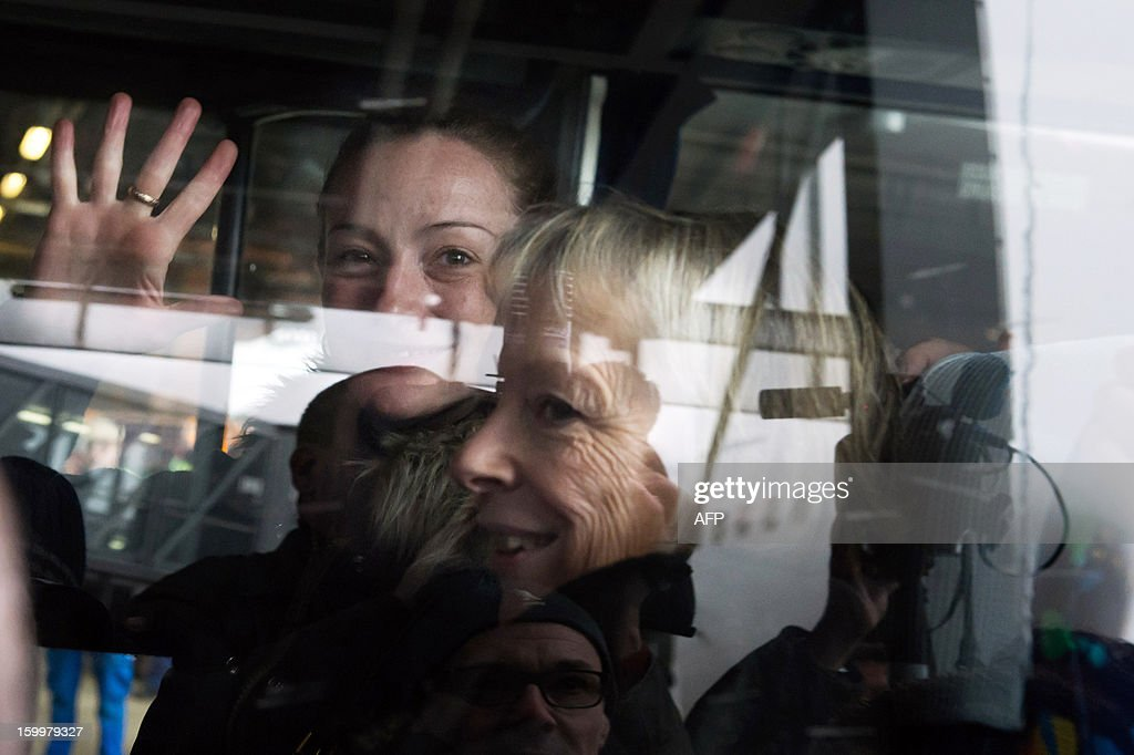 France's Florence Cassez gestures waves from a minivan, next to her mother Charlotte, at Roissy airport on January 24, 2013 in Roissy-en-France where she landed after being freed from a Mexican prison the day before following a Supreme Court ruling that police violated her rights by staging her arrest for kidnapping on national television seven years ago. After facing 60 years in jail, Cassez, 38, took a flight to Paris, hours after three of five justices voted for her immediate release in a case that had strained Franco-Mexican ties.