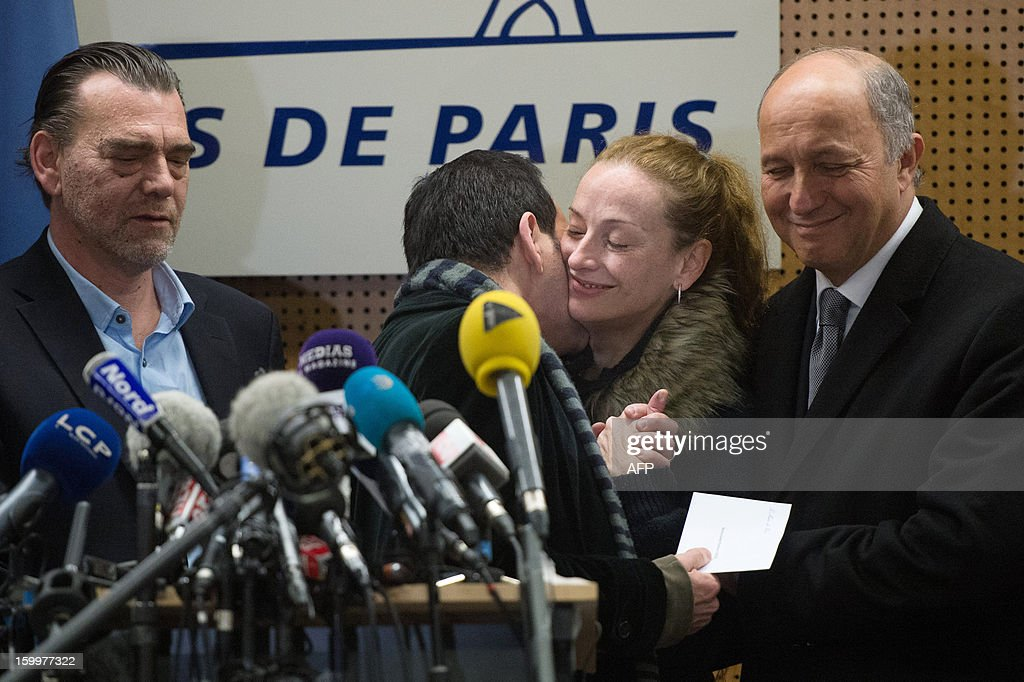 France's Florence Cassez (2nd R) is kissed by Jean-Luc Romero (L), President of her support comitee, next to French Foreign minister Laurent Fabius (R) and her Lawyer Frank Berton, during a press conference at Roissy airport on January 24, 2013 in Roissy-en-France where she landed after being freed from a Mexican prison the day before following a Supreme Court ruling that police violated her rights by staging her arrest for kidnapping on national television seven years ago. After facing 60 years in jail, Cassez, 38, took a flight to Paris, hours after three of five justices voted for her immediate release in a case that had strained Franco-Mexican ties.