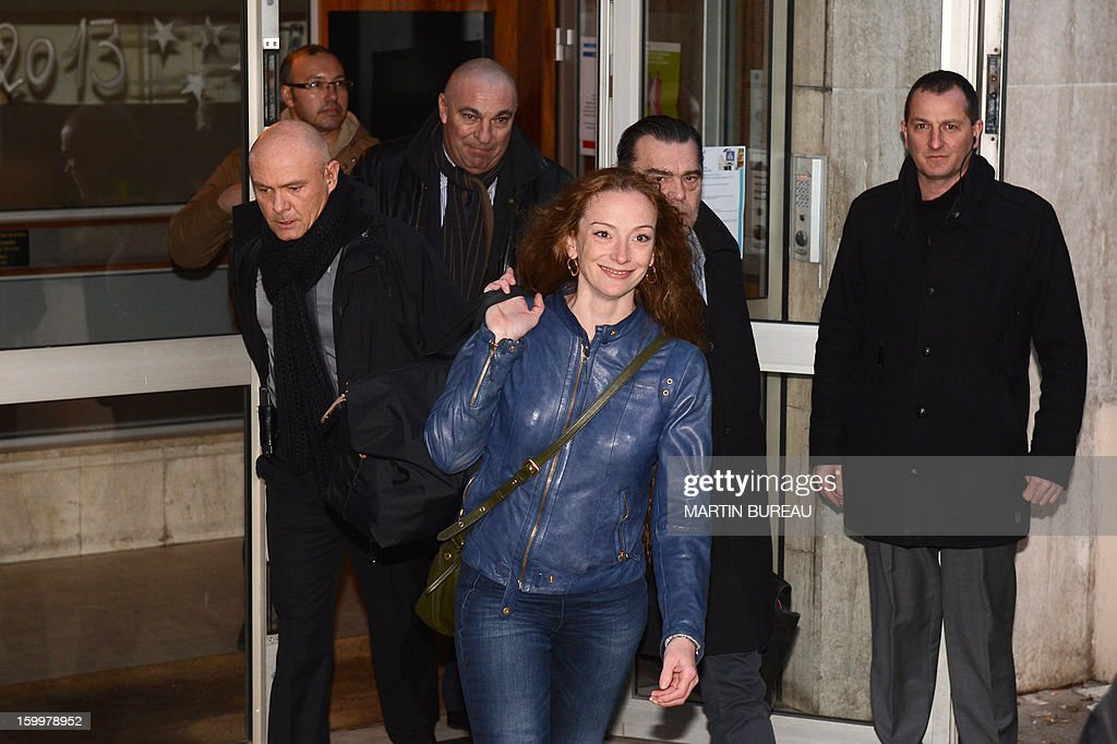 France's Florence Cassez (C) leaves an appartment building shortly after arriving in France on January 24, 2013 in Paris, after being freed from a Mexican prison the day before following a Supreme Court ruling that police violated her rights by staging her arrest for kidnapping on national television seven years ago. After facing 60 years in jail, Cassez, 38, took a flight to Paris with her father Bernard, hours after three of five justices voted for her immediate release in a case that had strained Franco-Mexican ties. AFP PHOTO / MARTIN BUREAU