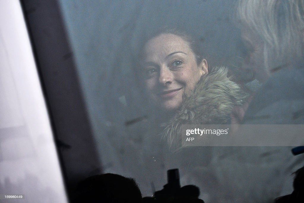 France's Florence Cassez smiles from a minivan at Roissy airport on January 24, 2013 in Roissy-en-France where she landed after being freed from a Mexican prison the day before following a Supreme Court ruling that police violated her rights by staging her arrest for kidnapping on national television seven years ago. After facing 60 years in jail, Cassez, 38, took a flight to Paris, hours after three of five justices voted for her immediate release in a case that had strained Franco-Mexican ties.