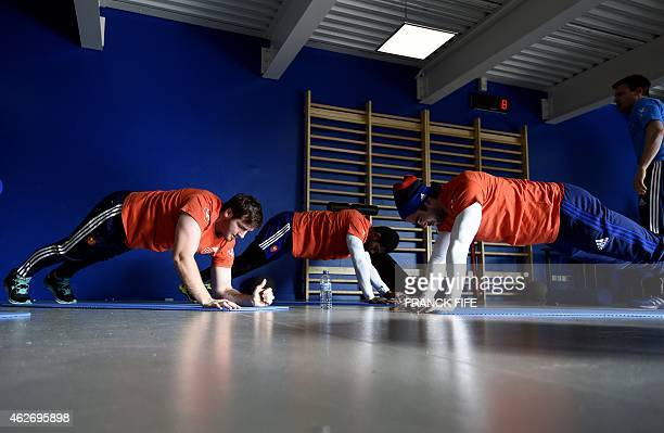 France's fly half Camille Lopez and France's wing Yoann Huget perform stretching exercises attends in an indoor training session on February 3 2015...