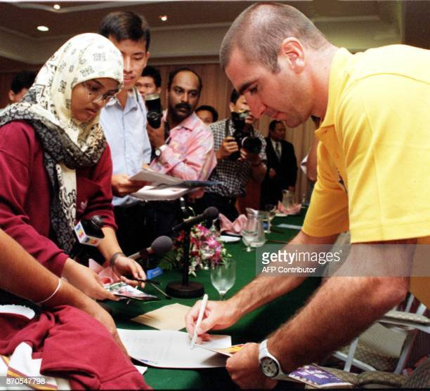 France's football star Eric Cantona sign autographs for his Malaysian fans after a news conference in Kuala Lumpur 21 May Cantona is here to take...