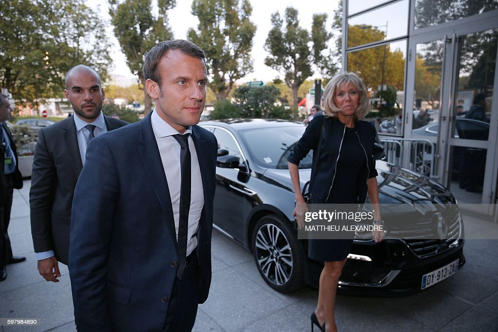 France's former Minister of the Economy Emmanuel Macron flanked by his wife Brigitte Trogneux arrives at the TF1 headquarters before taking part in...