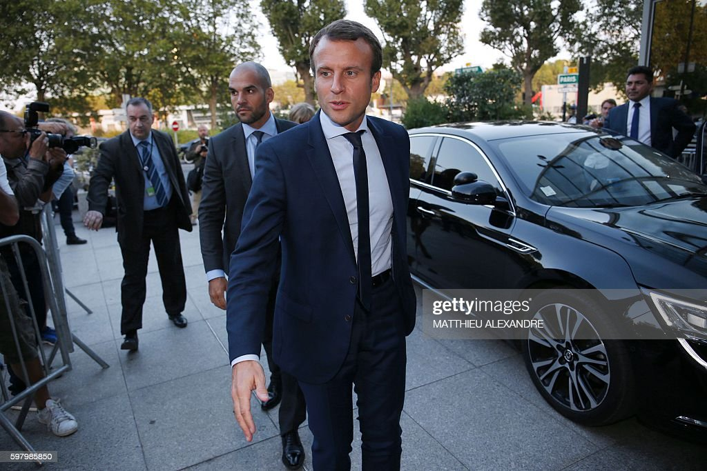 France's former Minister of the Economy Emmanuel Macron gestures as he arrives at the TF1 headquarters before taking part in the broadcast news of...