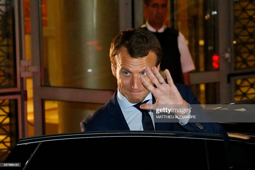 France's former Minister of the Economy Emmanuel Macron gestures as he leaves the TF1 headquarters after taking part in the broadcast news of the...