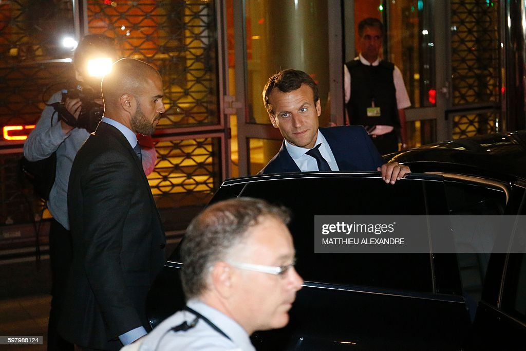 France's former Minister of the Economy Emmanuel Macron looks on as he leaves the TF1 headquarters after taking part in the broadcast news of the...