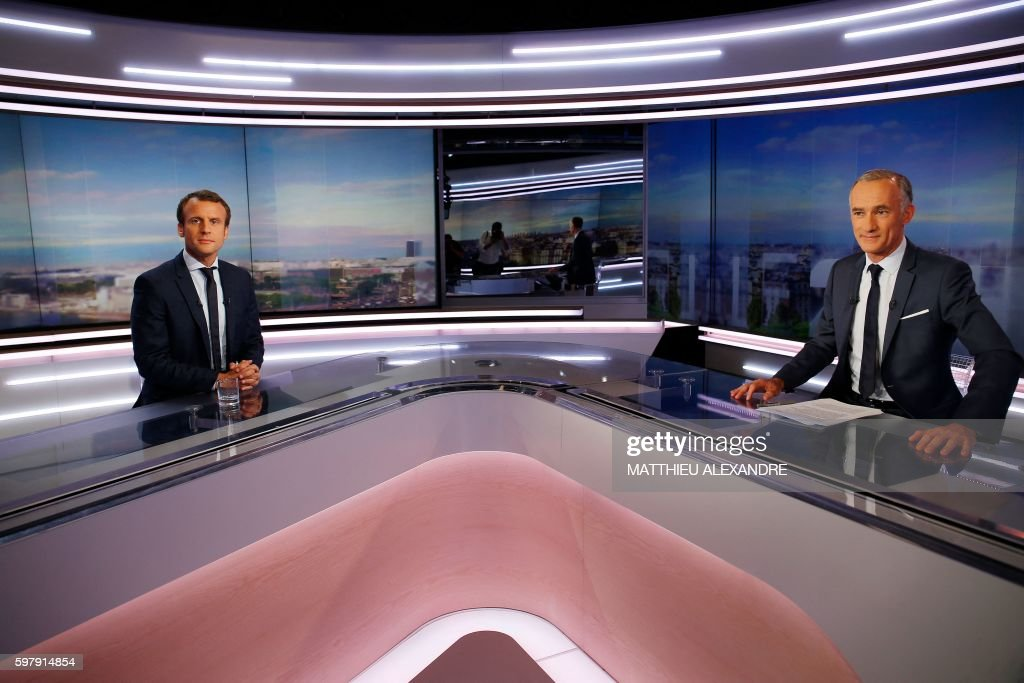France's former Minister of the Economy Emmanuel Macron looks on before taking part in the broadcast news hosted by Gilles Bouleau of the French...