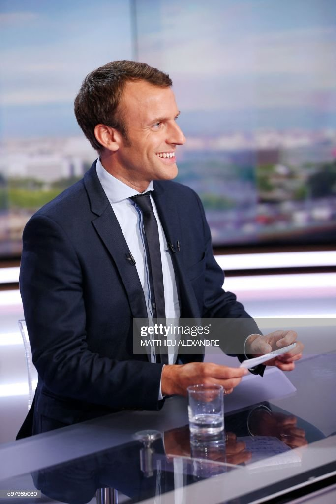 France's former Minister of the Economy Emmanuel Macron reacts before taking part in the broadcast news of the French television channel TF1 in...