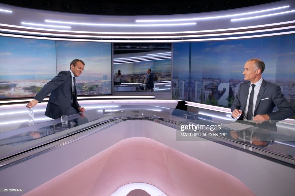 France's former Minister of the Economy Emmanuel Macron sits down before taking part in the broadcast news hosted by Gilles Bouleau of the French...