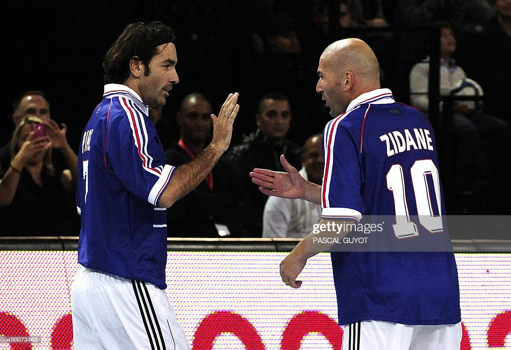 France's former national football team players Zinedine Zidane (R) and Robert Pires (L) celebrate after a goal during a futsal match between the French champions of the 1998 World Cup and Nantes at the Park Suites Arena in Montpellier in southern France on November 16, 2013.