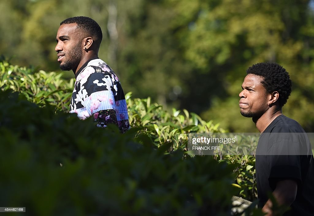 France's forward Alexandre Lacazette (L) and France's forward Loic Remy arrive at the French national football team training base in Clairefontaine on September 1, 2014 on the first day of their training ahead of the friendly football match against Spain to be held on September 4.