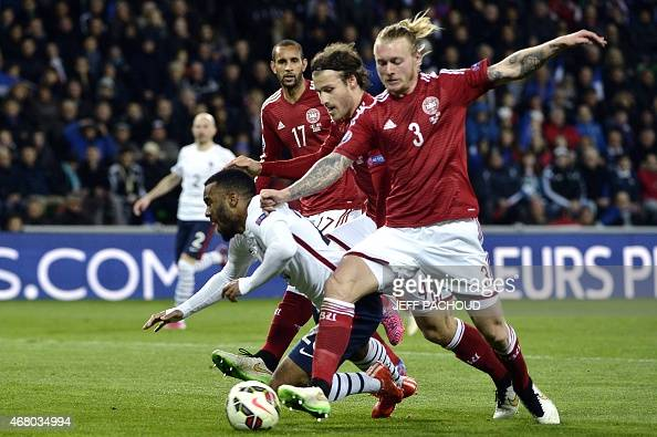 France's forward Alexandre Lacazette is tackled by Denmark's defender Simon Kjaer during the friendly football match between France and Denmark on...