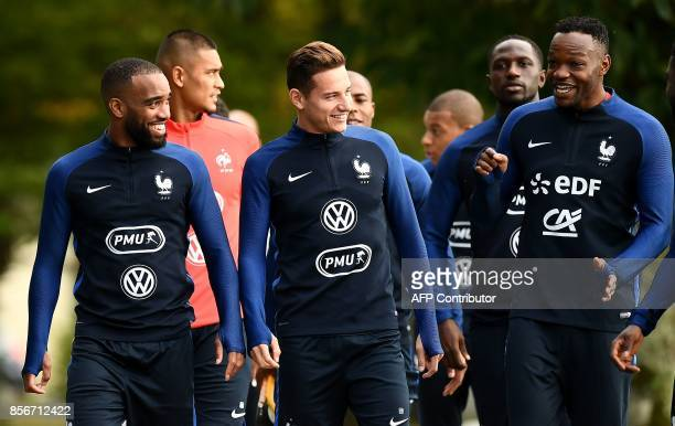 France's forward Alexandre Lacazette jokes with France's forward Florian Thauvin and France's goalkeeper Steve Mandanda before a training session in...