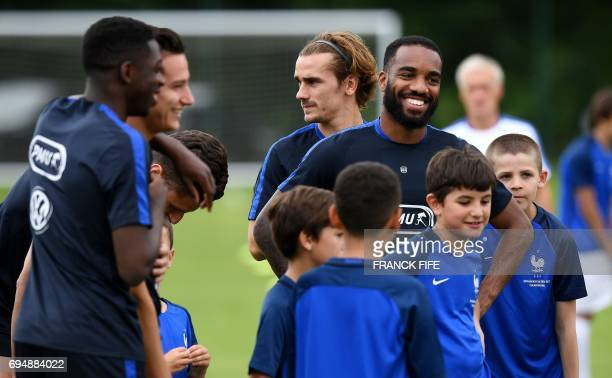 France's forward Alexandre Lacazette jokes with young players before a training session in ClairefontaineenYvelines near Paris on June 11 two days...
