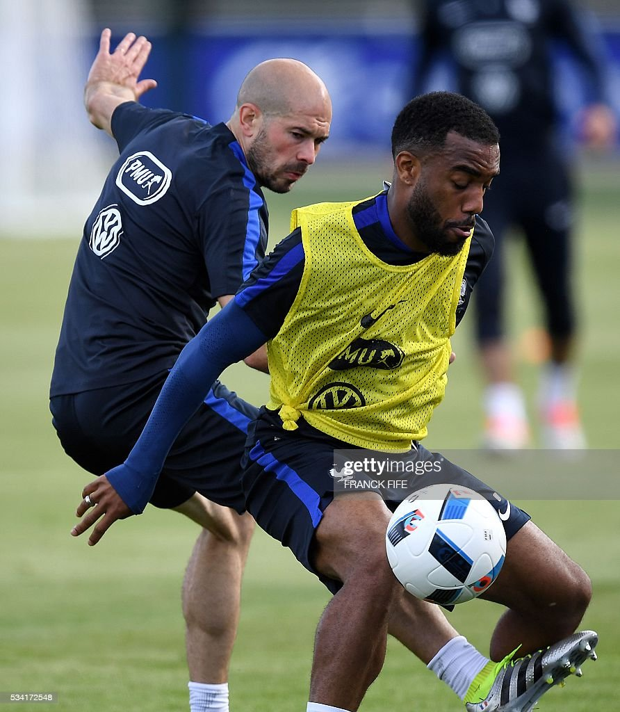 France's forward Alexandre Lacazette (R) vies with France's defender Christophe Jallet (L) during a training session in Clairefontaine as part of the team's preparation for the upcoming Euro 2016 European football championships, on May 25, 2016. / AFP / FRANCK