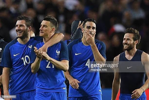 France's forward Andre Pierre Gignac defender Laurent Koscielny defender Adil Rami and midfielder Yohan Cabaye react after winning the friendly...