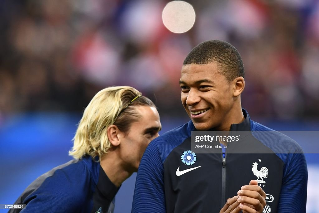 France's forward Antoine Griezmann (L) and France's forward Kylian Mbappe (R) laugh prior to the friendly football match between France and Wales at the Stade de France stadium, in Saint-Denis, on the outskirts of Paris, on November 10, 2017. /