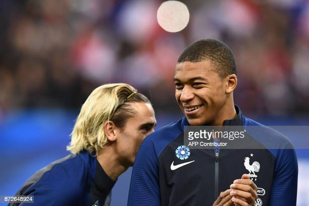 France's forward Antoine Griezmann and France's forward Kylian Mbappe laugh prior to the friendly football match between France and Wales at the...