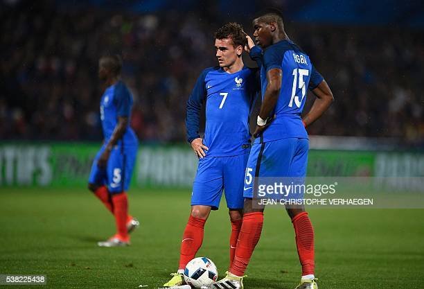 France's forward Antoine Griezmann and France's midfielder Paul Pogba react during the friendly football match between France and Scotland at the...