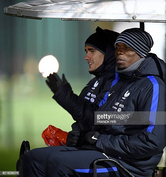 France's forward Antoine Griezmann and France's midfielder Paul Pogba leave a training session in ClairefontaineenYvelines near Paris on November 7...