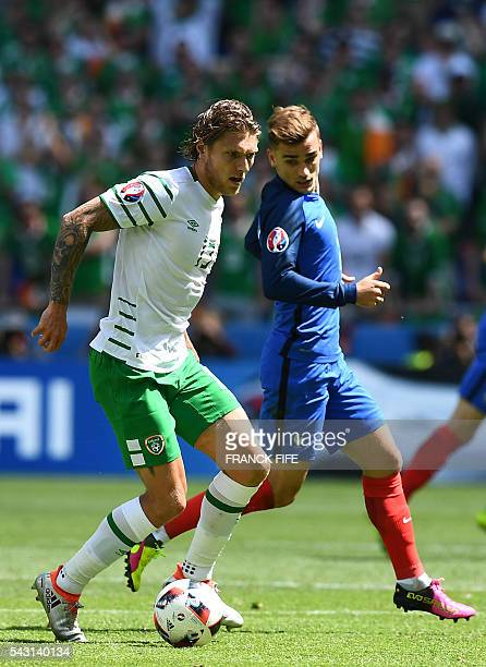 France's forward Antoine Griezmann and Ireland's midfielder Jeffrey Hendrick vie for the ball during the Euro 2016 round of 16 football match between...