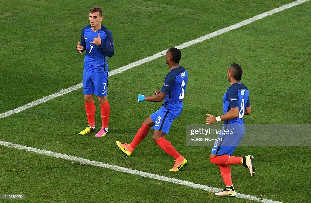 France's forward Antoine Griezmann celebrates after scoring a penalty next to France's defender Patrice Evra and France's forward Dimitri Payet...