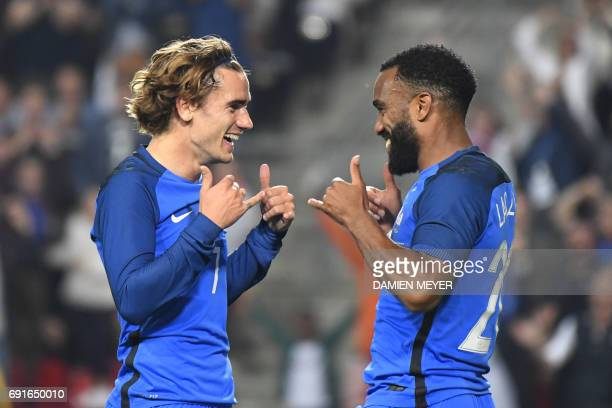 France's forward Antoine Griezmann celebrates with France's forward Alexandre Lacazette after scoring a goal during the friendly football match...